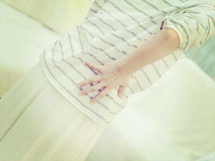 腰が痛くて手でおさえている女性