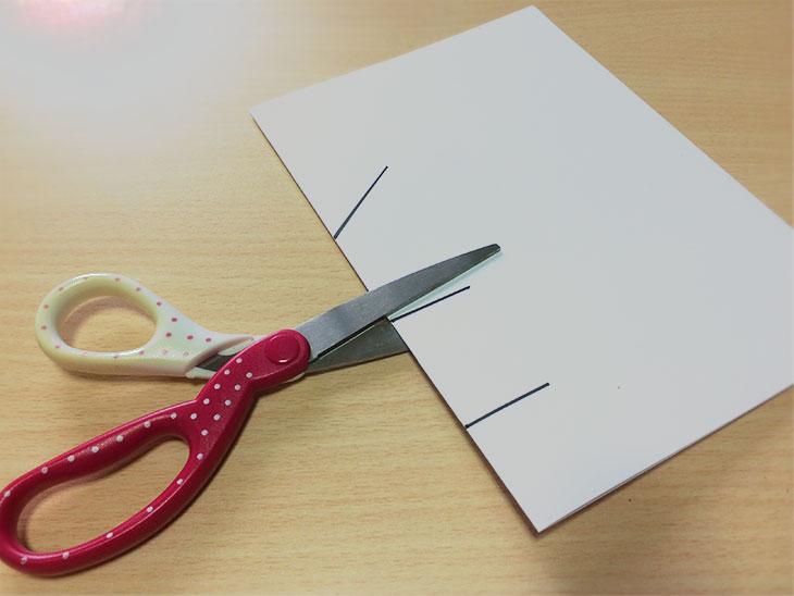 半分に折った紙の折り目にハサミで切り込みを入れる