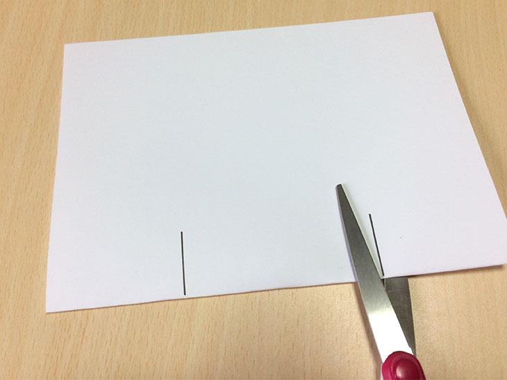 半分に折った紙の折り目にハサミで2箇所切り込みを入れる