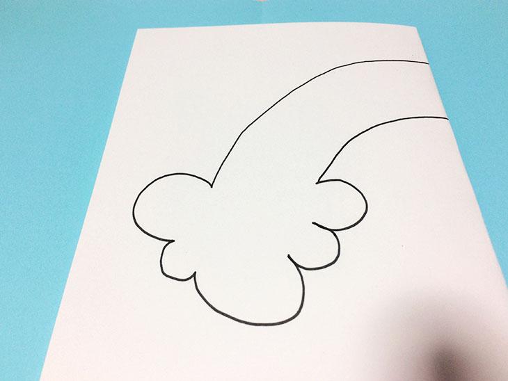 半分に折った白い紙に雲から伸びる虹の絵を描く