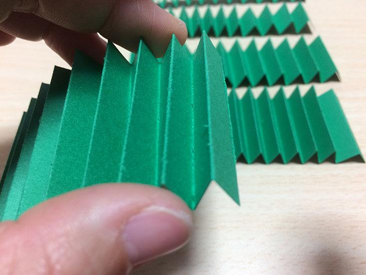 ジャバラ折りした緑の紙の端っこを飛び出す絵本のベースとなる半分に折った紙にノリで接着する