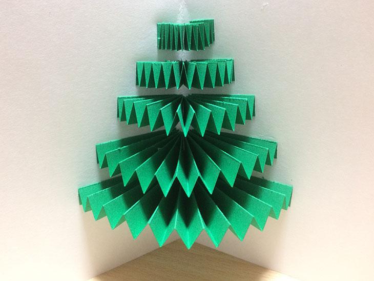 長さの違うジャバラ状の緑の紙を5個接着したクリスマスツリーの飛び出す絵本のベース
