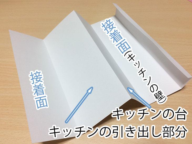 半分に折った白い紙の半分に山折り1個ともう半分に谷折り2箇所を入れる