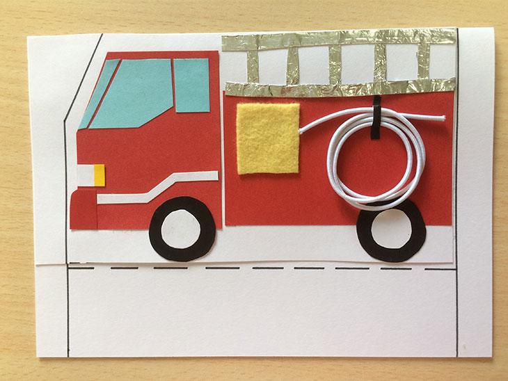 半分に折った白い紙に赤や黒などの紙を切り貼りして消防車の形を作る