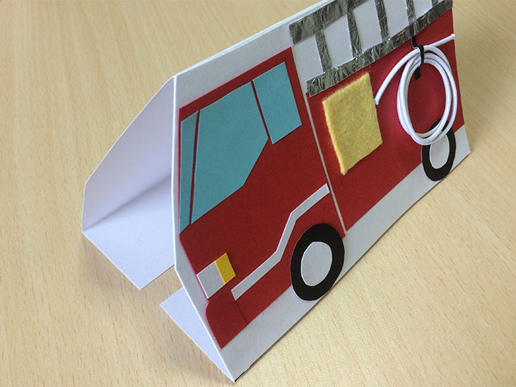 消防車の形に切った白い紙の端をベース紙につけるノリシロを折り込む