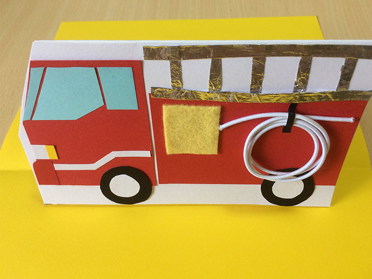 黄色いベース紙に消防車の形を作った白い紙を接着する