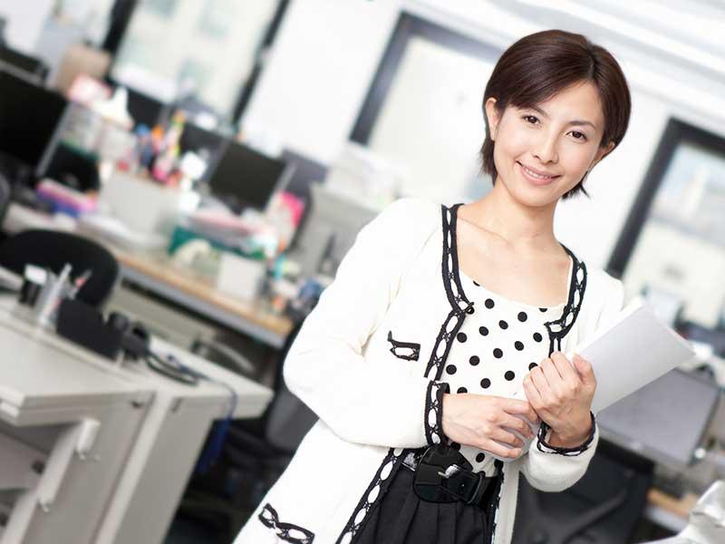 書類を手にして働いている女性