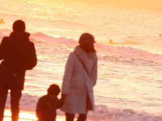 夕日にたたずむ子供と家族