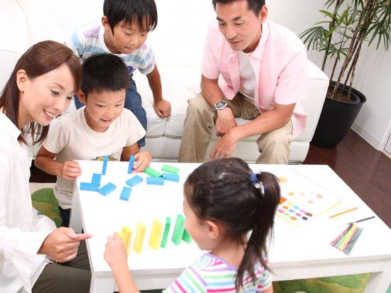 テーブルの上で遊ぶ子供と笑顔で見守る父親と母親