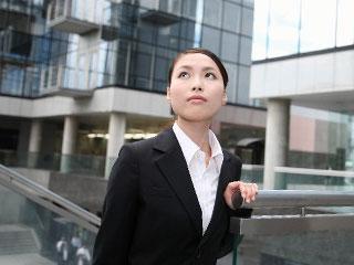 上を見上げるスーツの女性