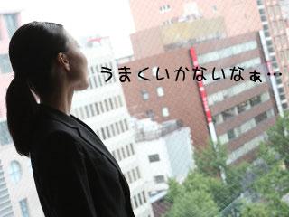 会社から外を眺めて考えるスーツ姿の女性