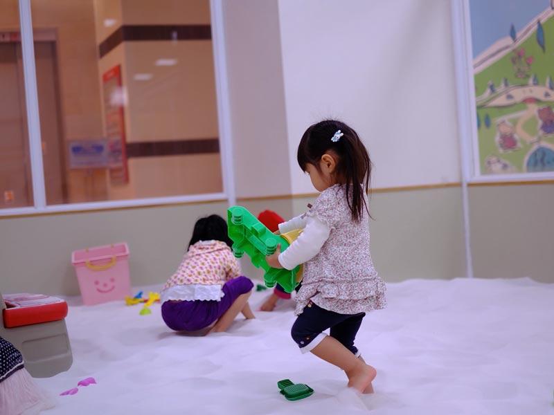 室内砂遊び場でおもちゃを持ちながら歩く女の子