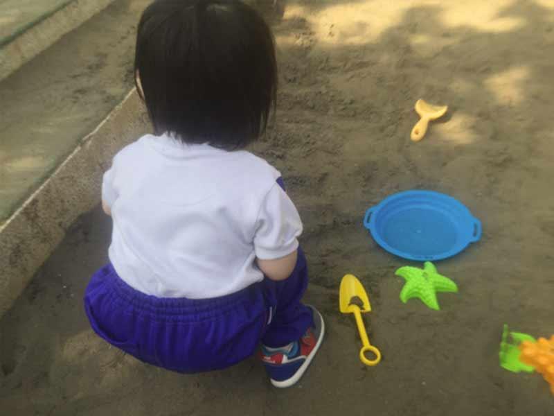 砂場にしゃがむ子供