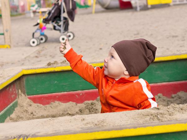 砂場で砂を掴む男の子