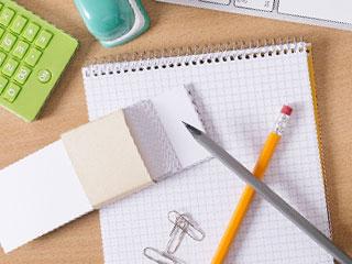 机に置かれた家計簿と鉛筆と電卓
