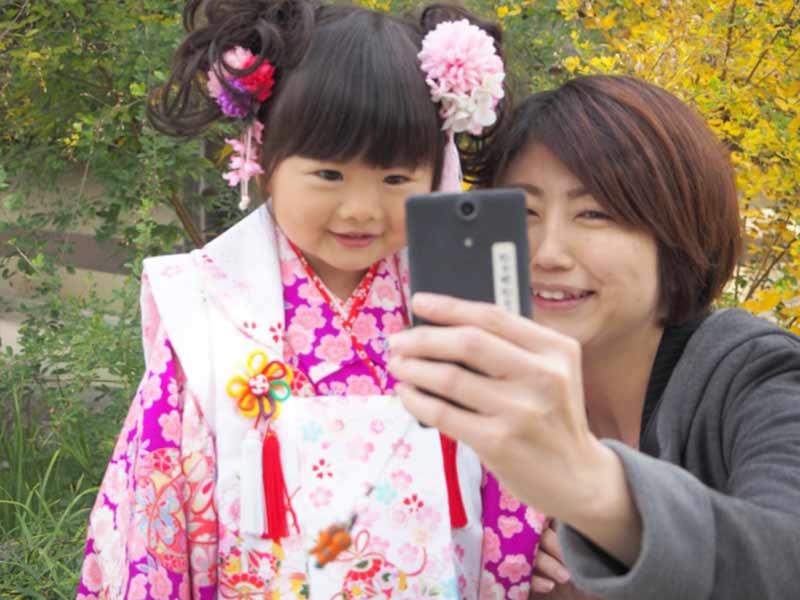3歳の七五三の娘と携帯で写真を撮るお婆さん