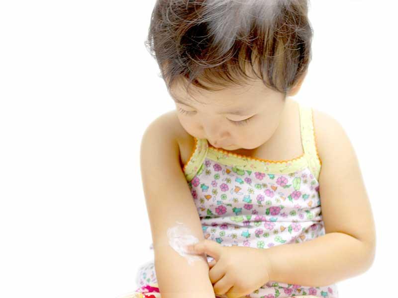 自分の腕にローションを塗る小さい女の子