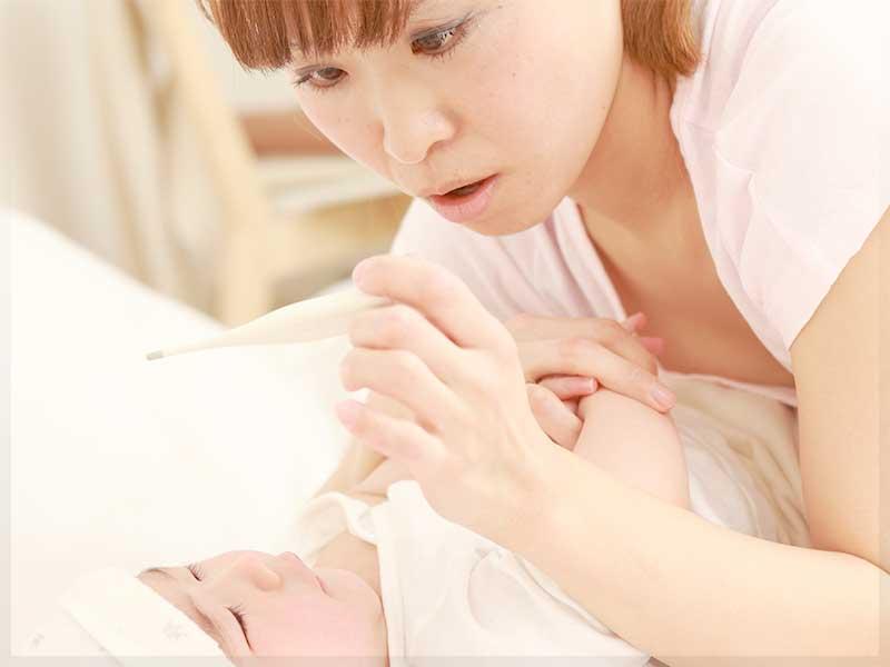 赤ちゃんの熱を測るママ