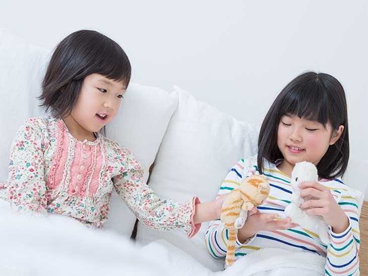 お泊り会の日にベッドの中で遊んでいる女の子たち