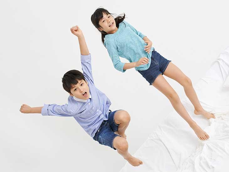 ソファーの上でジャンプしている女の子と男の子