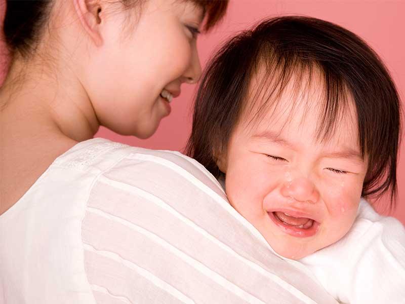 お母さんに抱っこしてもらいながら泣く女の子