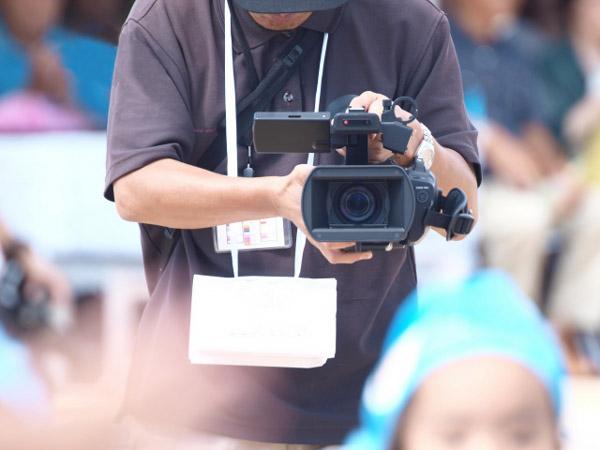 運動会を撮影してるパパ
