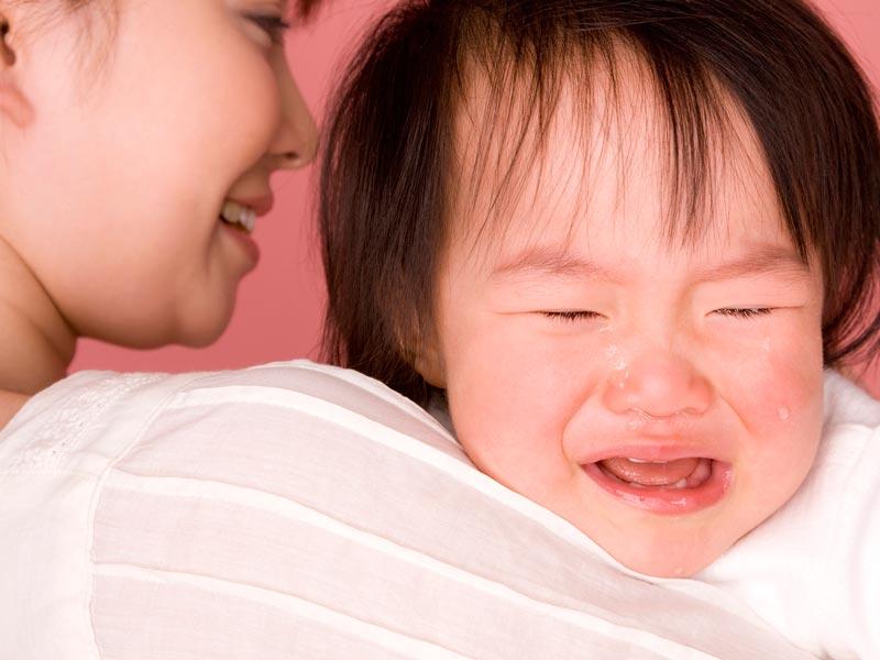 ママに抱っこされながら泣いてるこども