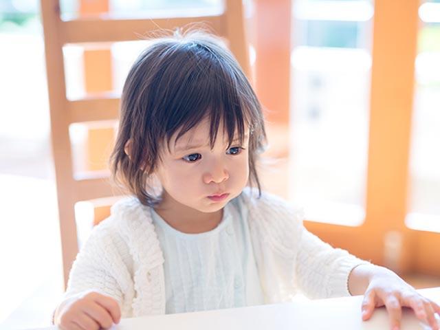 椅子に座って黙り込む幼児