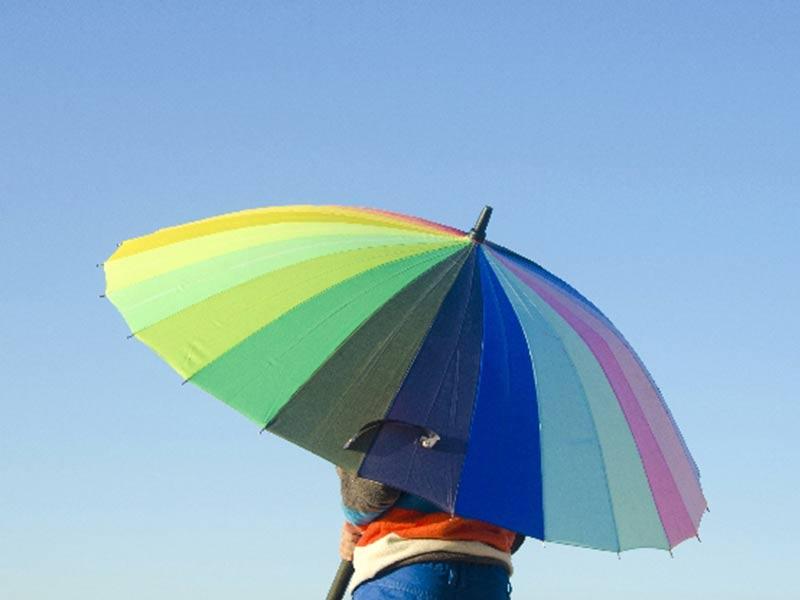 カラフルな傘を差す男の子