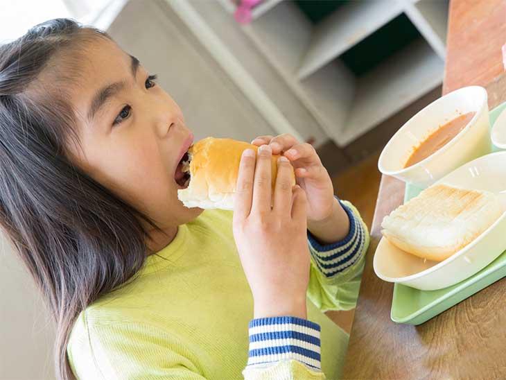 給食のコッペパンを食べようとしている女の子