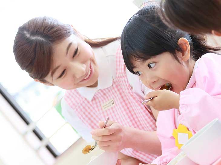 幼稚園で給食を食べている女の子