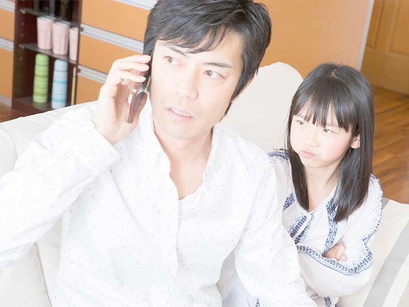 子供を無視しながら電話を取る夫