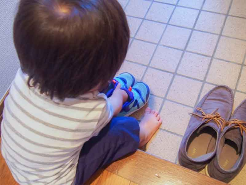 玄関で靴を履く小さい男の子