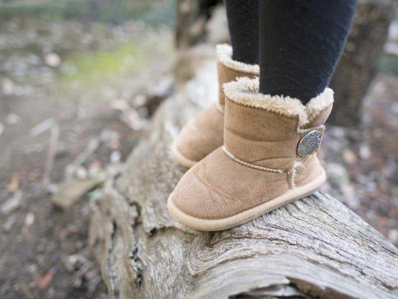 朽木に登るブーツを履いた女の子の足