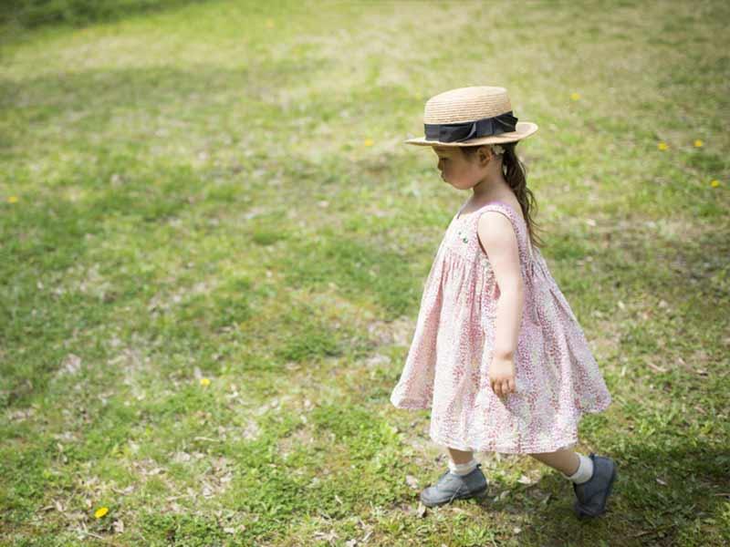 草原を歩く帽子をかぶった小さい女の子