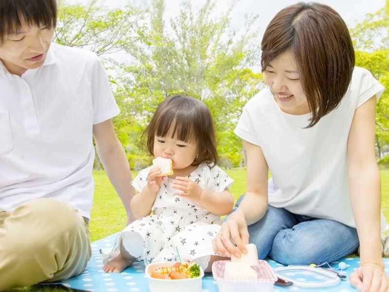 公園でピクニックをする3人家族