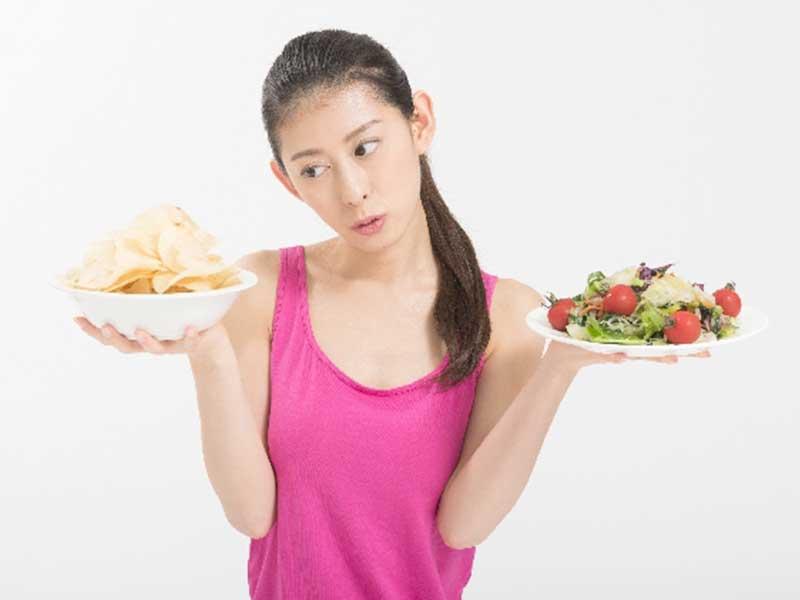 サラダとスナックを持つ女性