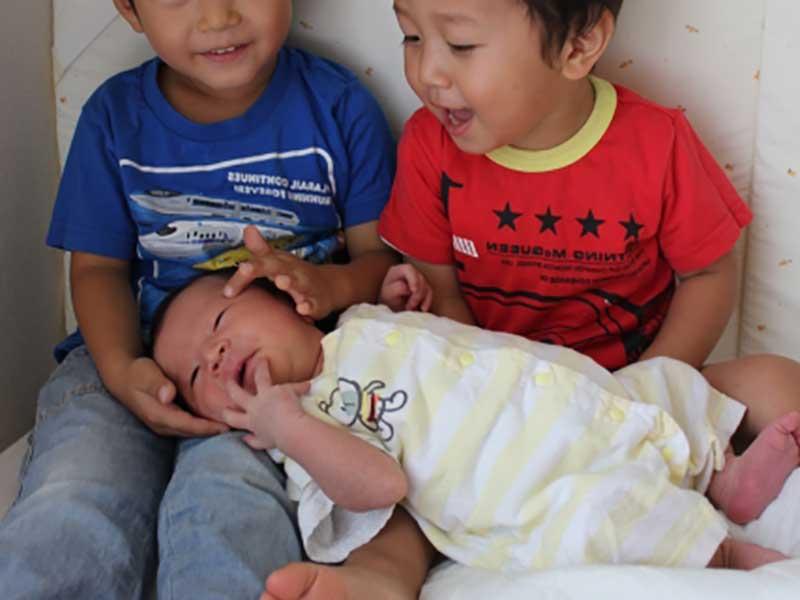 赤ちゃんの様子を見てる子供達