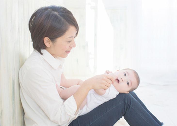 新生児を膝に乗せてあやしている母親