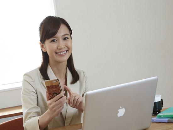パソコンと携帯を操作する笑顔でこっちを見る女性