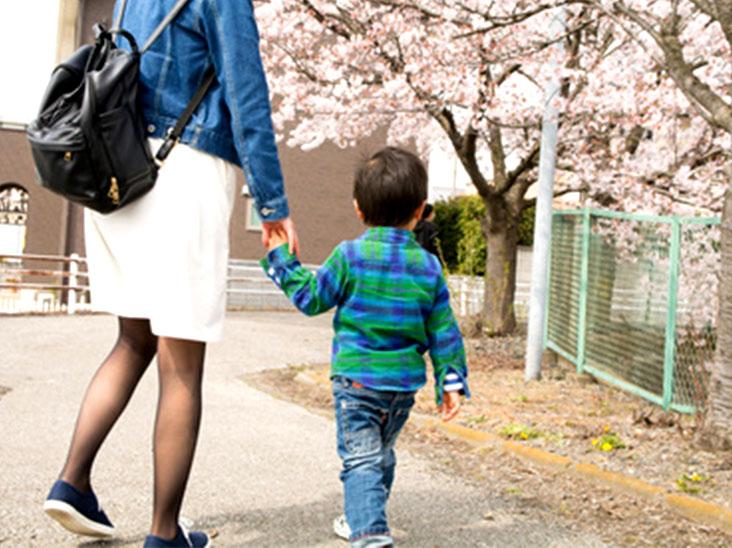 母親に手を惹かれて歩いている幼児